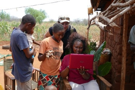 Nashon and his family looking at camera trap footage of the elephants that visited their farm