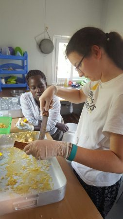 Tanya with Kenyan intern Esther uncapping the capped honey