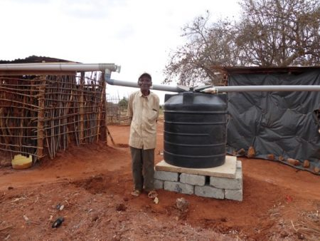 Nzai standing proudly with his new water tank