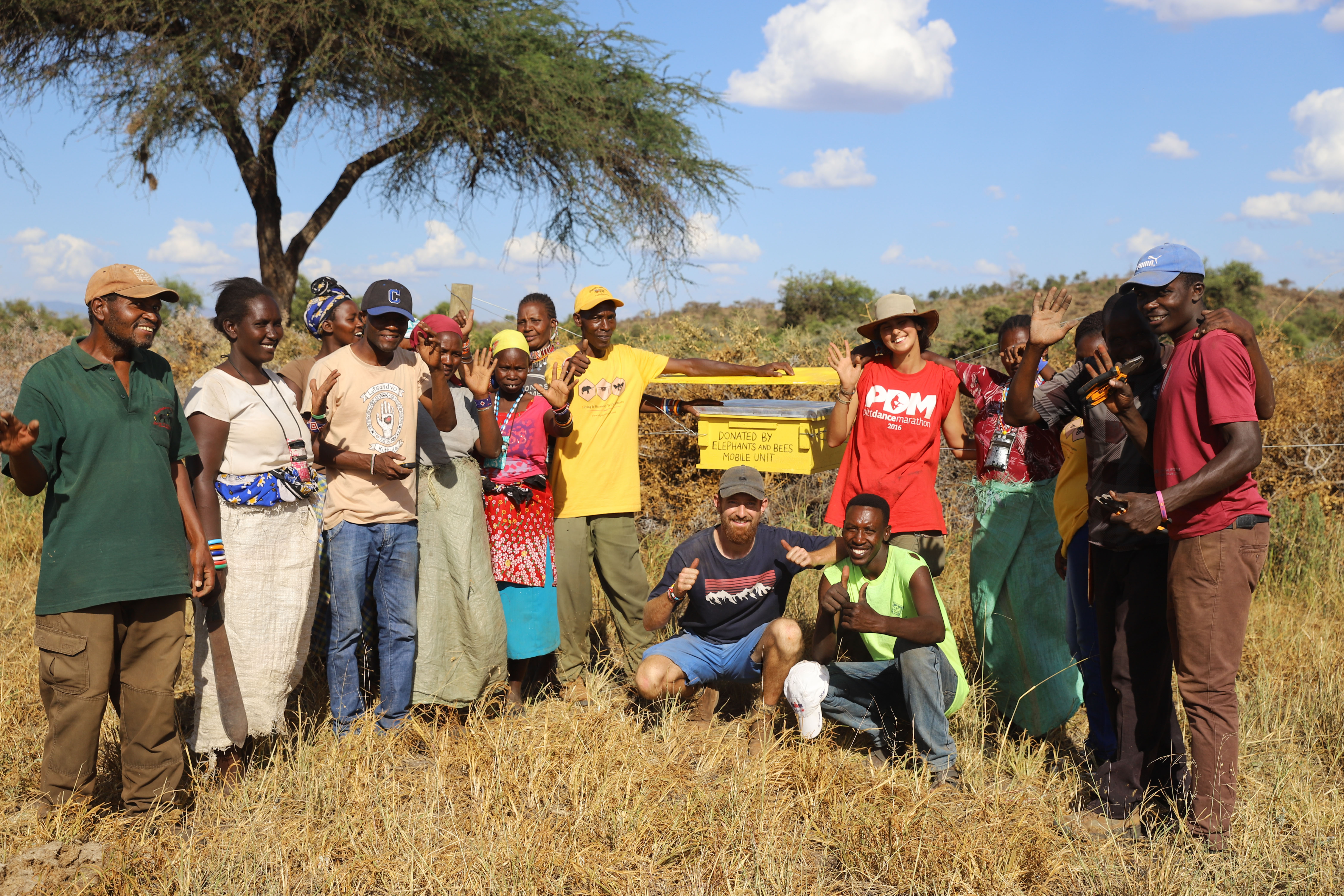 A-group-photo-next-to-a-beehive-fence-after-beehive-fence-construction-in-the-Chyulu-Hills_MWCT12-©-2019-Naiya-Raja